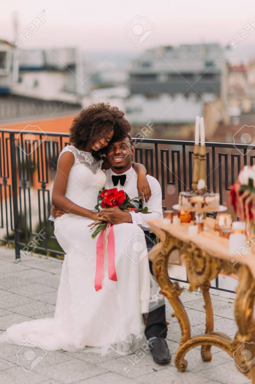 Charming black wedding couple tenderly hugging on the rooftop.
